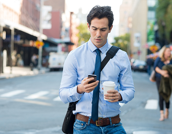 Man walking and looking at his phone.